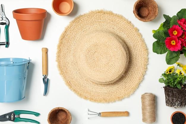 園芸工具および白いテーブル、トップビューでアクセサリーを構成