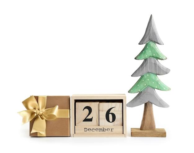 Композиция с подарочной коробкой, календарем и деревянной елкой, изолированной на белом
