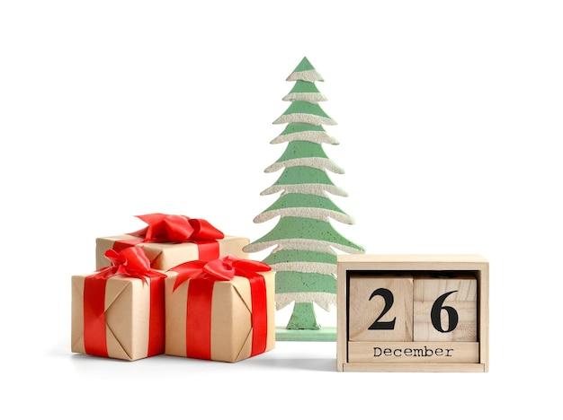 Композиция с подарочными коробками, календарем и деревянной елью, изолированной на белом