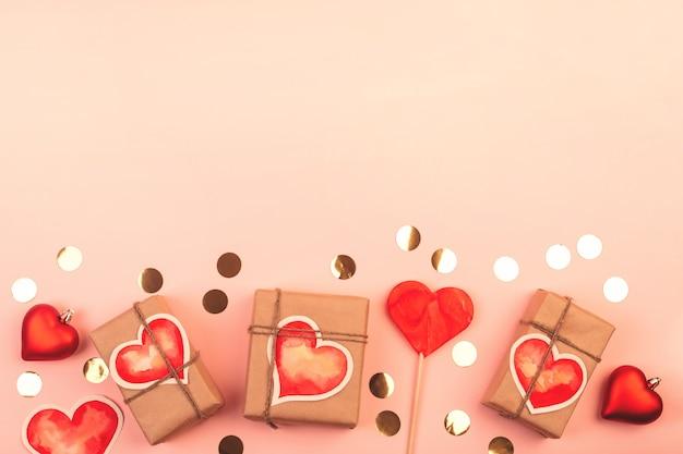 Композиция с подарочными коробками, стеклянными сердечками, леденцом на палочке и золотым конфетти на розовом. фон с копией пространства на день святого валентина.
