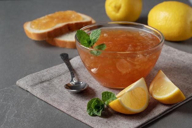 Композиция со стеклянной миской домашнего лимонного джема на сером столе