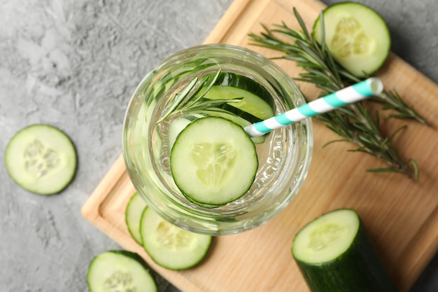 Composition with glass of cucumber water on grey surface