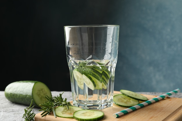 Composition with glass of cucumber water on grey table