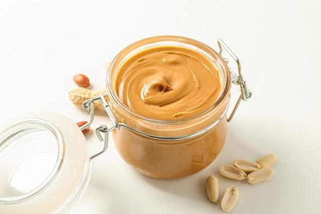 Композиция со стеклянной банкой с арахисовым маслом и арахисом