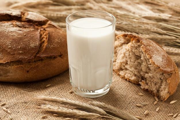 Композиция со стаканом молока, хлебом и колосьями ржи на мешковине.