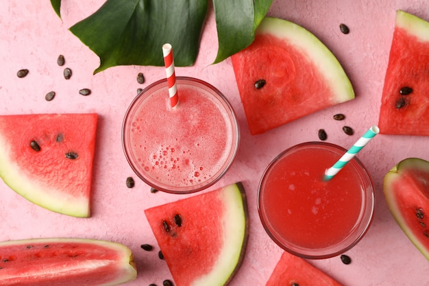 Composition with glass of watermelon juice and slices on pink table
