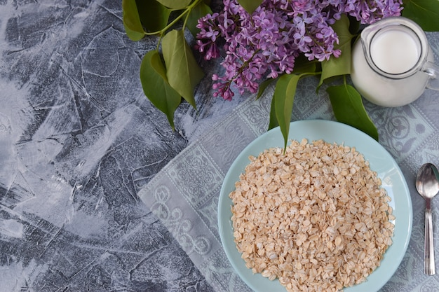 皿の上のグラノーラ、牛乳のデカンター、コピースペース上面とライラックの小枝の組成物。