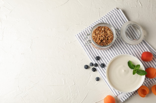 Composition with granola, yogurt and fresh fruits on white cement background