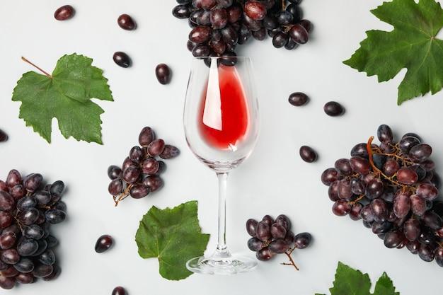 Композиция с виноградом и бокалом вина на белом