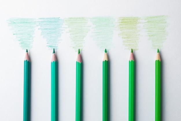 Композиция с зелеными карандашами разных цветов на светлом фоне. вид сверху