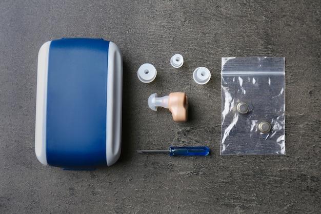 Композиция со слуховым аппаратом и аксессуарами на сером