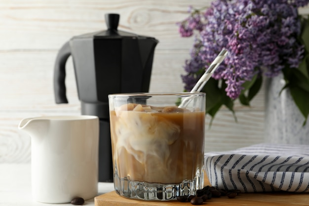 Composition with ice coffee and flowers on white wooden