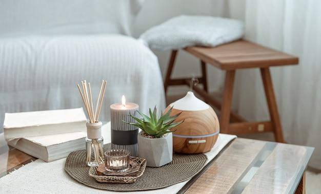 Композиция с ароматическими палочками, диффузором, свечами и книгами на столе в интерьере комнаты.
