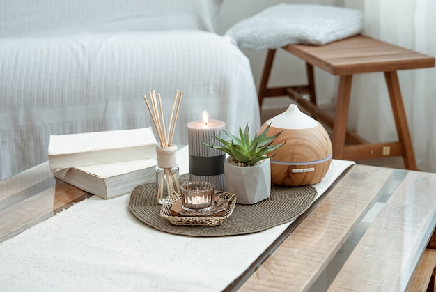Composition with incense sticks, diffuser, candles and books on the table in the interior of the room.