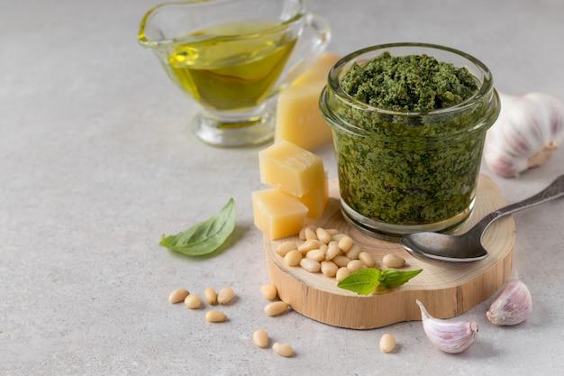 Композиция с банкой вкусного зеленого соуса песто и ингредиентами на сером столе
