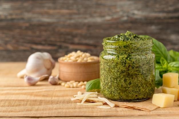 Композиция с банкой зеленого соуса песто и ингредиентами на деревянном столе