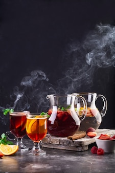 Composition with jugs and glasses with hot drinks, fruits, berries and mint.