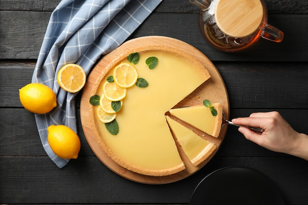 Composition with lemon tart on dark wooden background, top view
