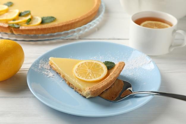 흰색 나무 배경에 접시에 레몬 타트 슬라이스 구성을 닫습니다
