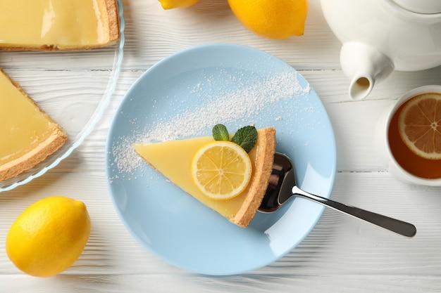 흰색 나무 배경, 평면도에 접시에 레몬 타르트 슬라이스 구성