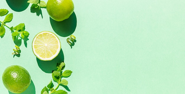 Composition with limes and mint in the morning light. trendy sunlight shadows. top view with copy space for text.