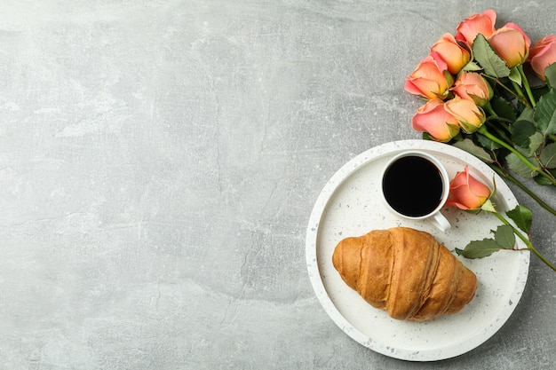 Composition with marble tray, cup of coffee, croissant, roses, top view