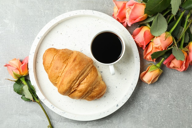 Composition with marble tray, cup of coffee, croissant and roses, top view