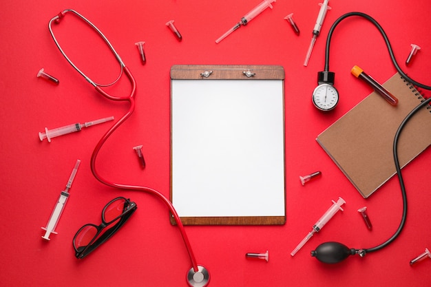 Composition with medical supplies and clipboard on color background