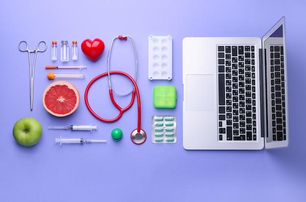 Композиция с медикаментами, едой и ноутбуком на цветном фоне