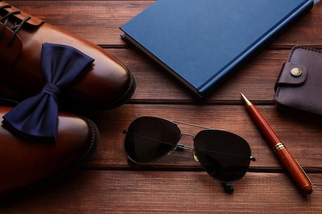 メンズアクセサリーとの構成メンズシューズ蝶ネクタイメガネメモ帳財布と木製テーブルのペン