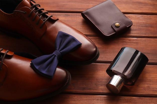 Композиция с мужскими аксессуарами мужская обувь, галстук-бабочка, очки, духи и кошелек на деревянном столе