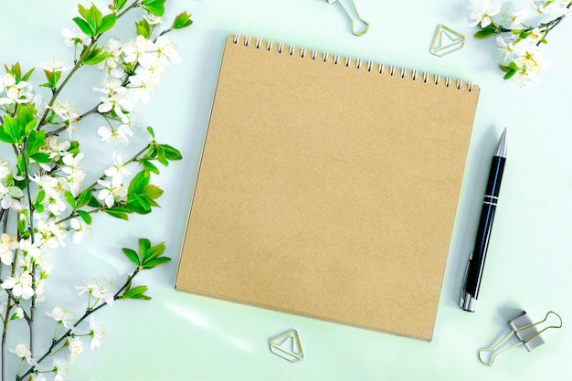 A composition with a mock-up of a blank page of a kraft paper notebook, pen and office clips with a blossoming cherry branch with flowers on a pastel blue background. top view.