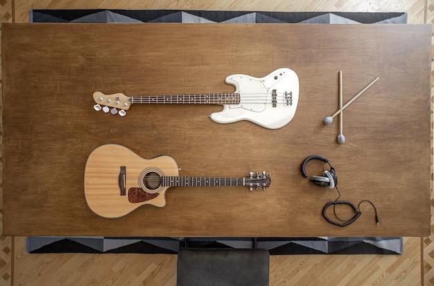 レコーディングスタジオの大きな木製テーブルで楽器を使って作曲。音に取り組むミュージシャンの職場。