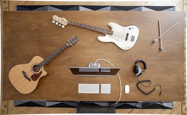 Композиция с музыкальными инструментами на большом деревянном столе в студии звукозаписи. рабочее место музыканта для работы над звуком.
