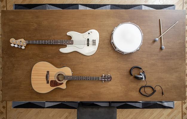 Композиция с музыкальными инструментами на большом деревянном столе в студии звукозаписи.