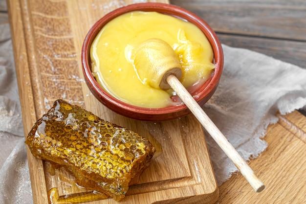 Composizione con miele naturale e mestolo di miele su fondo in legno si chiuda.