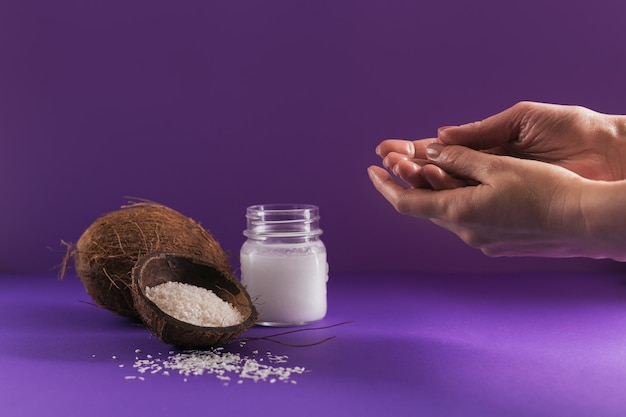 Composition with natural organic coconut oil cosmetic body cream on purple color background