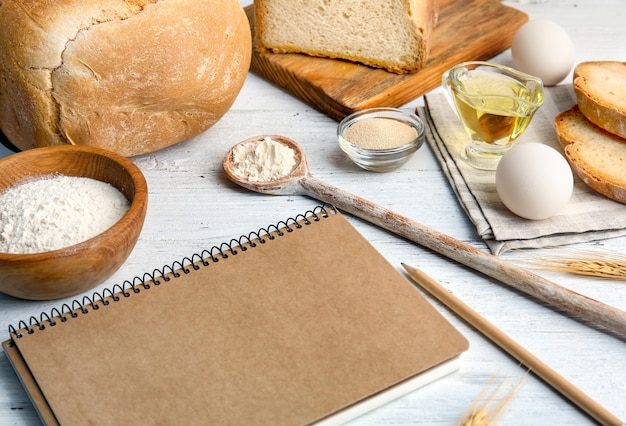 ノートと木製のテーブルの上のパンの材料との構成