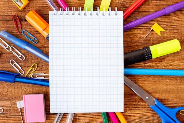 Состав с карандашем пустой страницы тетради красочным, отметка, ручка и космос экземпляра. обратно в школу концепции.