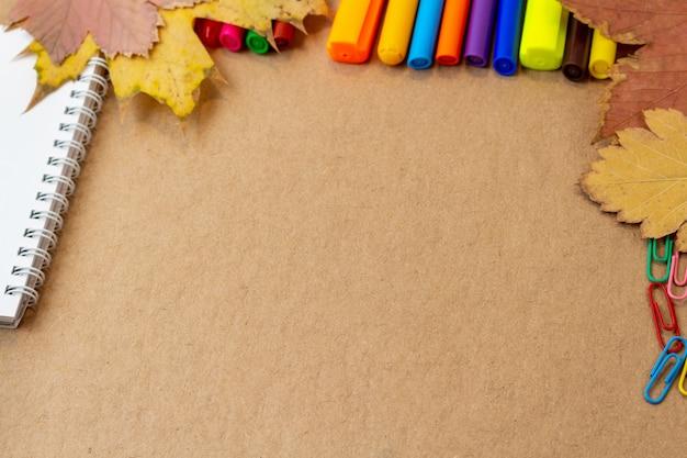 Композиция с блокнота пустой страницы красочными карандашами, фломастерами и ручками