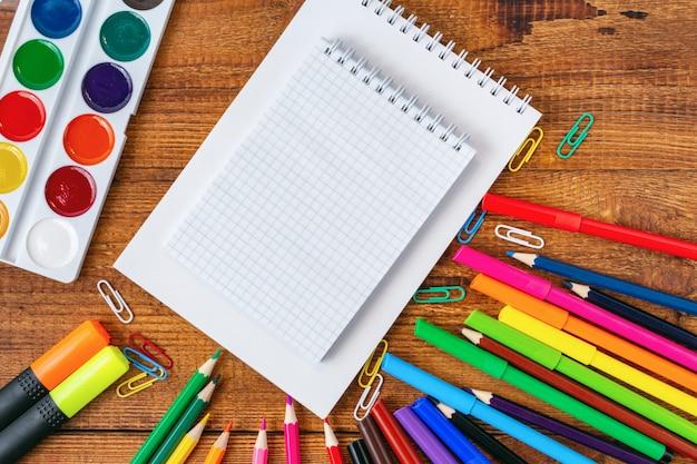 Композиция с тетрадью пустая страница красочные карандаши, маркеры и ручки