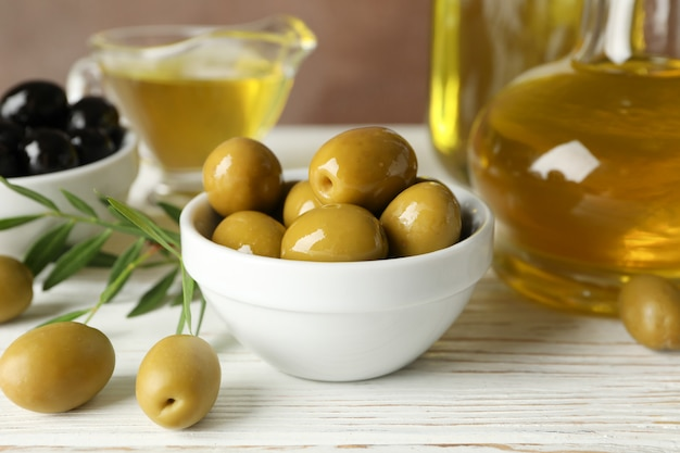 Composition with olive oil and olives on wooden table, close up