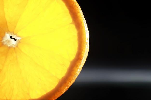 Композиция с дольками апельсина и грейпфрута на черном фоне. долька апельсина с подсветкой на черном фоне с каплями воды. сочный апельсин на столе.