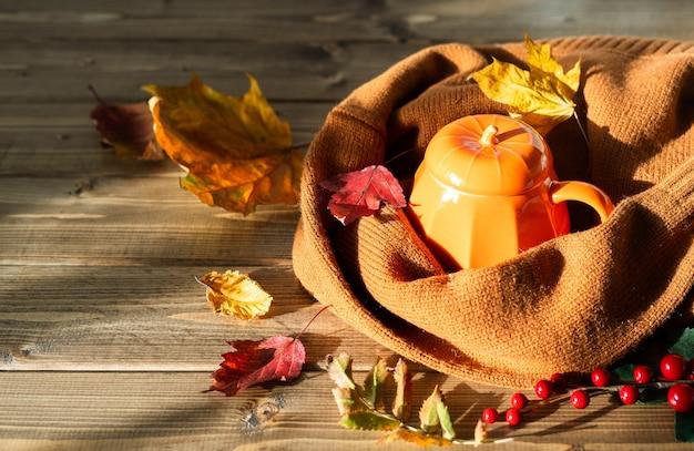 Композиция с оранжевой тыквой в стиле чашки кофе и осенним тематическим оформлением опавших листьев уютно