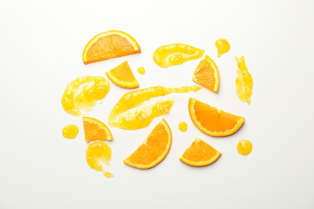Composition with orange slices and jam on white