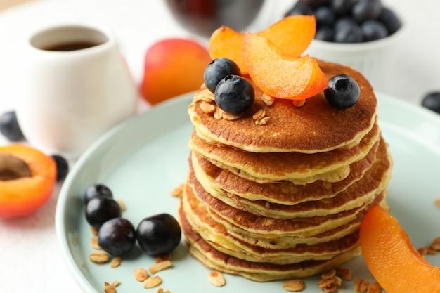 Композиция с блины и фрукты на белом столе. сладкий завтрак