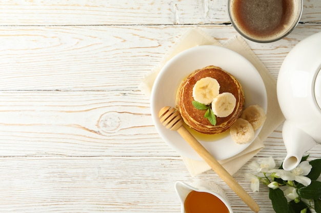 Композиция с блинами на белом деревянном столе, вид сверху. сладкий завтрак