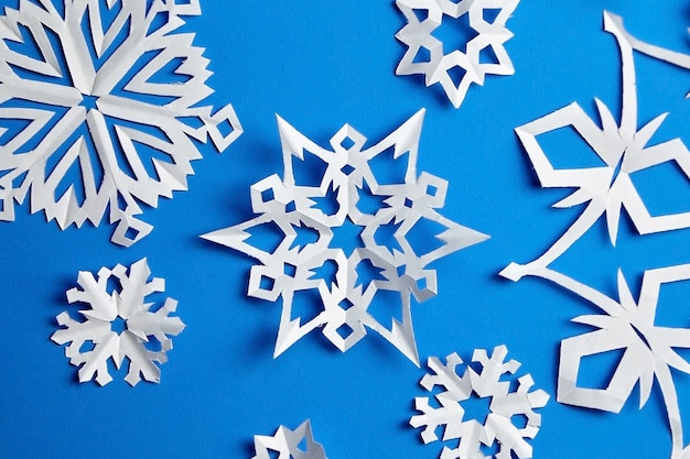 Composition with paper snowflakes on blue paper