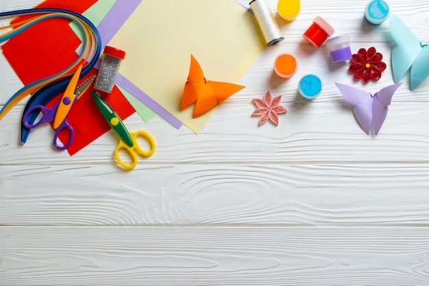 Composition with papercraft supplies on wooden white desk for kids activity