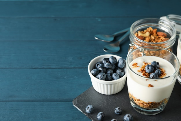 Composition with parfaits desserts on blue wooden background,
